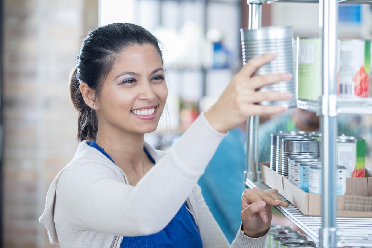 Mid adult Asian woman stocks food bank storeroom.